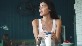 Trinkender Kaffee der jungen attraktiven Frau von einer Papierschale an der Kaffeestube stock video