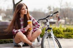Trinkender Kaffee der jungen Frau auf einer Fahrradreise Stockfoto