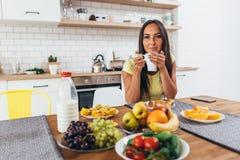 Trinkender Kaffee der jungen Frau auf der Küche morgens, die Kamera betrachtet Lizenzfreie Stockbilder