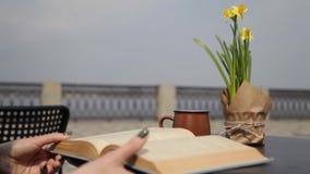 Trinkender Kaffee der jungen Frau, ein Buch lesend und treiben durch die Seiten in einem Straßencafé Blätter und genießen die Ans stock video