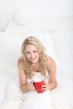 Trinkender Kaffee der jungen Frau im Bett Stockfotografie