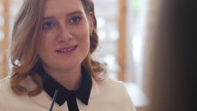Trinkender Kaffee der jungen Frau und das Sprechen mit frien im Café stock footage