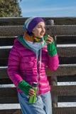 Trinkender Kaffee der jungen Frau von einer Thermosflascheschale auf einem Winter morni stockbilder