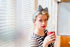 Trinkender Kaffee der schönen blonden lustigen Pinupfrau zu Hause Stockfotos