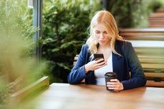 Trinkender Kaffee der Schönheit in einem Café und in einem Telefon stockbild