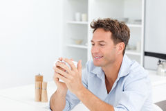 Trinkender Kaffee des attraktiven Mannes, der an einem Tisch sitzt lizenzfreies stockbild
