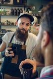 Trinkender Kaffee des engagierten Herrenfriseurs mit seinem Kunden und Freund Stockfoto