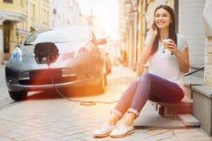 Trinkender Kaffee des Fahrzeughalters und Unterhaltung am Telefon Stockbild