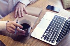 Trinkender Kaffee des Geschäftsmannes und Arbeiten an Laptop-Computer, Handy, Unternehmensplan schreibend, tragendes weißes Hemd lizenzfreies stockfoto