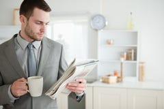 Trinkender Kaffee des Geschäftsmannes beim Lesen der Nachrichten Lizenzfreie Stockfotografie