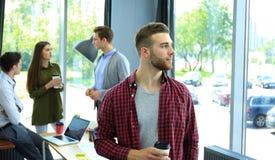 Trinkender Kaffee des glücklichen attracive jungen Geschäftsmannes im Büro lizenzfreie stockfotografie