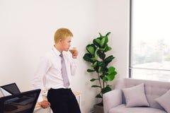 Trinkender Kaffee des glücklichen attracive jungen Geschäftsmannes im Büro stockfoto