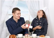 Trinkender Kaffee des glücklichen Paars und Habenspaß, Mann geben sehr lustige Geschenke - Liebes- und Feiertagskonzept Stockfotografie