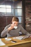 Trinkender Kaffee des gutaussehenden Mannes und Ablesenzeitung Stockbild