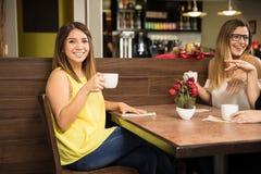 Trinkender Kaffee des hübschen Mädchens mit ihren Freunden stockfotos