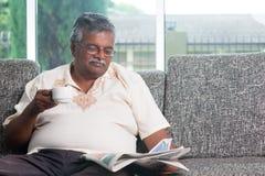 Trinkender Kaffee des indischen älteren Erwachsenen beim Ablesen des Nachrichtenpapiers Stockfoto