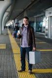Trinkender Kaffee des jungen attraktiven Mannes auf seiner Weise nahe dem Flughafenabfertigungsgebäude, das zur Kamera schaut lizenzfreies stockbild