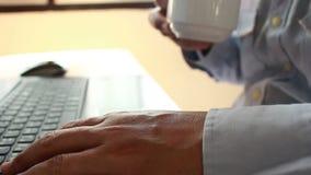 Trinkender Kaffee des jungen Geschäftsmannes und mit Laptop für Geschäftsarbeit in unscharfem Fokus stock video footage