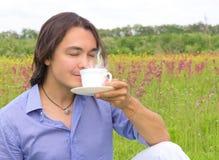Trinkender Kaffee des jungen glücklichen Mannes draußen Stockfotografie