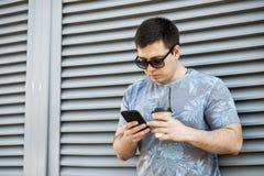 Trinkender Kaffee des jungen Mannes in der Stadt und Untersuchung einen Handy lizenzfreies stockbild