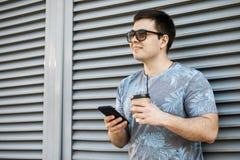 Trinkender Kaffee des jungen Mannes in der Stadt und Untersuchung einen Handy stockfoto