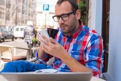 Trinkender Kaffee des jungen Mannes im Restaurant. Er hält einen Handy. Lizenzfreie Stockfotos