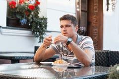 Trinkender Kaffee des jungen Mannes mit Hörnchen Stockbild
