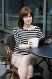 Trinkender Kaffee des Mädchens in einem Café im Freien Lizenzfreies Stockfoto