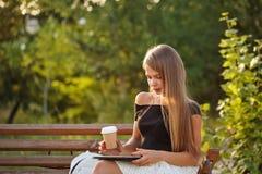 Trinkender Kaffee des Mädchens und Halten von Tabletten-PC Lizenzfreies Stockbild