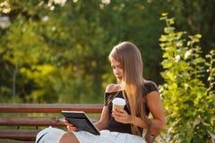 Trinkender Kaffee des Mädchens und Halten von Tabletten-PC Lizenzfreie Stockfotografie