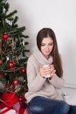 Trinkender Kaffee des Mädchens unter dem Tee des neuen Jahres des Weihnachtsbaums lizenzfreie stockfotos