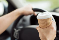 Trinkender Kaffee des Mannes beim Fahren des Autos stockfoto