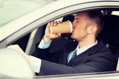 Trinkender Kaffee des Mannes beim Fahren des Autos Lizenzfreies Stockfoto