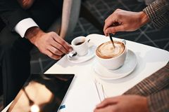 Trinkender Kaffee des Mannes und der Frau am Restaurant Kaffeetasse und handliche geöffnete Überausgabe lizenzfreie stockbilder