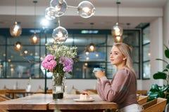 Trinkender Kaffee des schönen Mädchens im lokalen Café mit hölzernem Innenraum Stockfoto