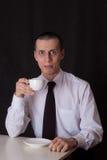Trinkender Kaffee des sonderbaren Geschäftsmannes Stockfoto