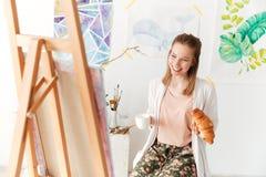 Trinkender Kaffee glücklichen Damenmalers, der Hörnchen isst Lizenzfreies Stockfoto