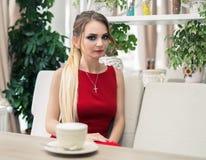 Trinkender Kaffee oder Tee der Geschäftsfrau im Restaurant Dame In Red Lizenzfreie Stockfotos