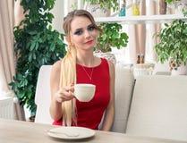 Trinkender Kaffee oder Tee der Geschäftsfrau im Restaurant Dame In Red Stockbilder