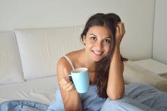 Trinkender Kaffee oder Tee des hübschen Mädchens des Porträts auf Bett morgens in der Wohnung mit Kopienraum Lizenzfreies Stockfoto