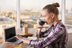 Trinkender Kaffee und Anwendung des Laptops Lizenzfreie Stockfotografie