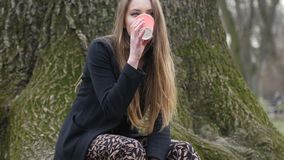 Trinkender Kaffee zum Mitnehmen der jungen stilvollen Blondine im Herbstpark Blattloser Baum auf Hintergrund stock footage