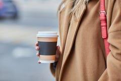 Trinkender Kaffee zum Mitnehmen der jungen stilvollen Frau in einer Stadtstra?e stockfoto