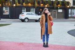 Trinkender Kaffee zum Mitnehmen der jungen stilvollen Frau in einer Stadtstra?e lizenzfreie stockbilder