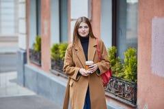 Trinkender Kaffee zum Mitnehmen der jungen stilvollen Frau in einer Stadtstra?e lizenzfreies stockbild