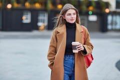 Trinkender Kaffee zum Mitnehmen der jungen stilvollen Frau in einer Stadtstra?e lizenzfreies stockfoto
