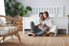 Trinkender Kakao der glücklichen liebevollen Paare auf Wintermorgen im Bett lizenzfreie stockfotografie