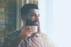 Trinkender Morgenkaffee des ehrfürchtigen Mannes Stockfoto
