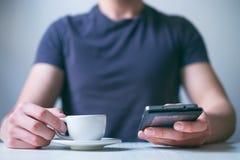 Trinkender Morgenkaffee des jungen Mannes und halten Handy Süßes Hörnchen und ein Tasse Kaffee im Hintergrund Bemannen Sie das Ha Lizenzfreies Stockbild