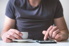 Trinkender Morgenkaffee des jungen Mannes und halten Handy Süßes Hörnchen und ein Tasse Kaffee im Hintergrund Bemannen Sie das Ha Stockfoto